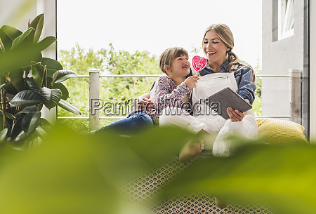 happy mother and daughter with tablet