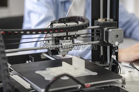 student setting up 3d printer close