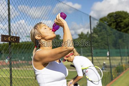 mature woman at tennis club taking