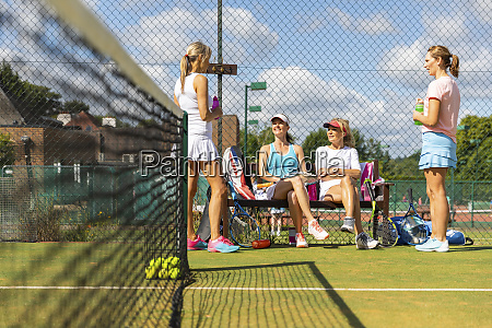 mature women at tennis club taking