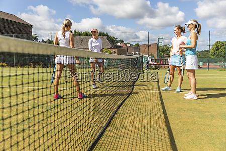 mature women talking on grass court