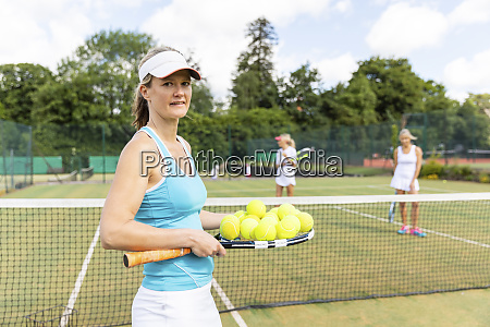 mature woman holding tennis balls and