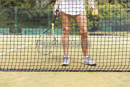 female tennis player legs on grass