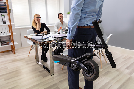 person carrying electric scooter in folded
