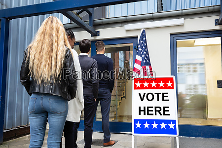 people standing outside voting room
