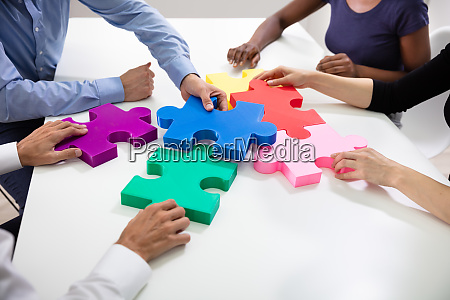 businesspeople building colorful jig saw puzzles