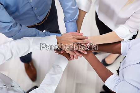 multiracial businesspeople stacking hands over each