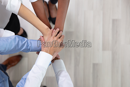 employees stacking hands together
