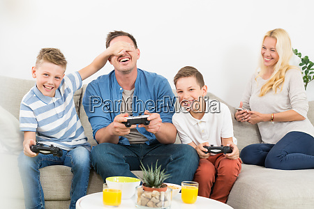 happy young family playing videogame on