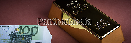 euro cash and gold bar on