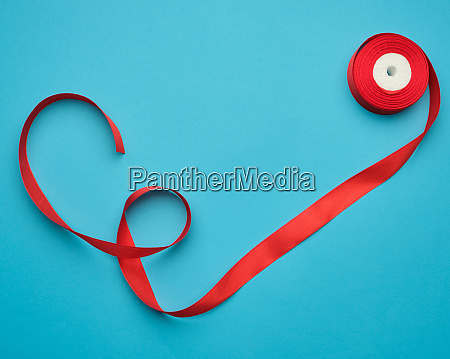 curled red satin ribbon on blue