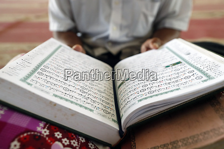 old man reading quran sitting on
