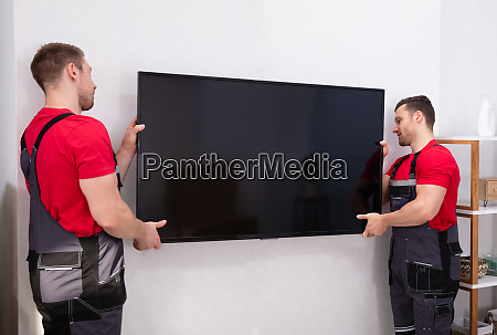 male movers fixing the large lcd