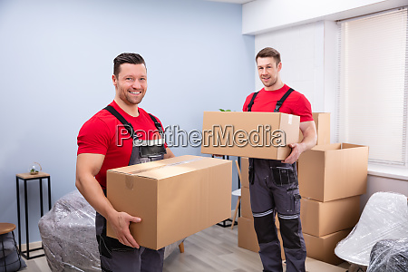 smiling young male relocation worker carrying