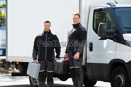 portrait of two male electrician carrying