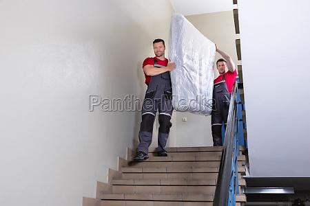 young men in uniform carrying mattress
