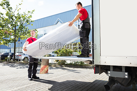 young men unloading the mattress from