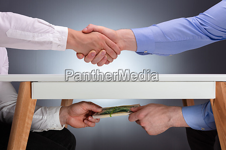 two businessmen shaking hands and receiving