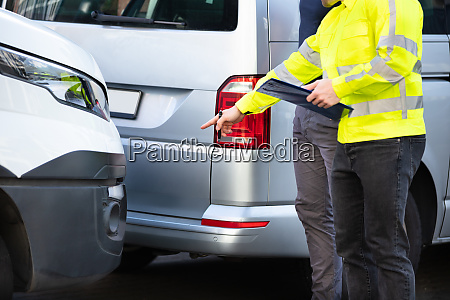 loss adjuster with clipboard inspecting damaged