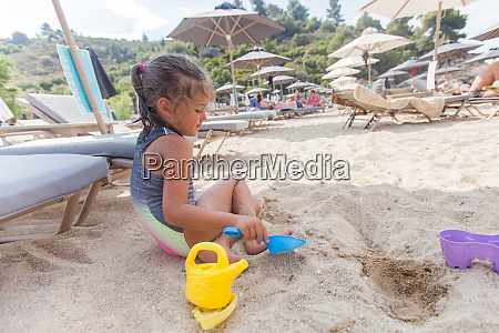 little girl playing with beach toys