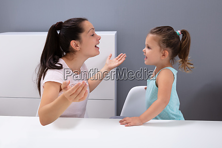 speech therapist helps the girl to