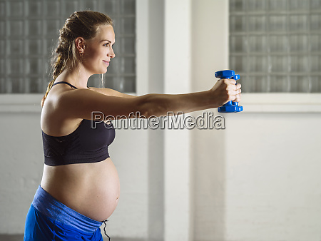 pregnant woman doing shoulder exercises with