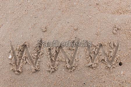 the word www handwritten in sand