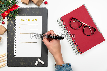 womans hand writing 2020 goals in