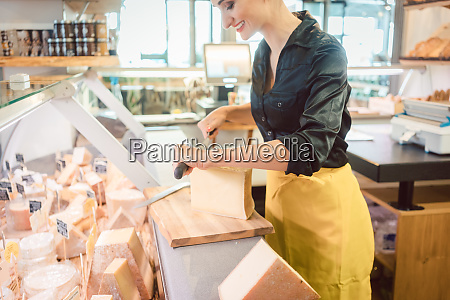 young shop clerk in deli cutting