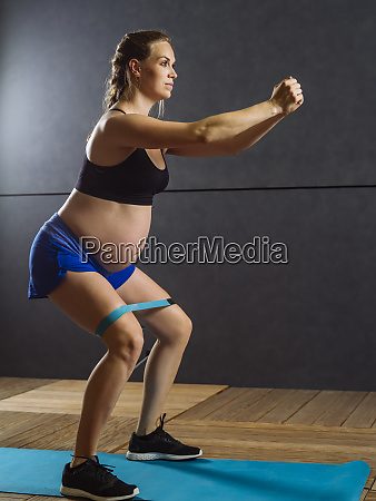 pregnant woman exercising her thighs with