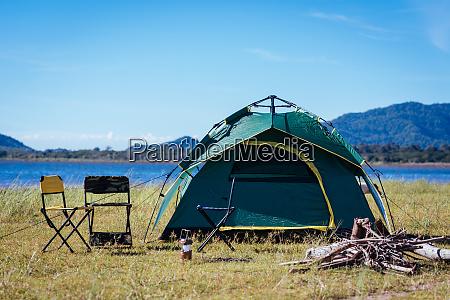 camping green tent near lake