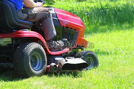 gardener driving a riding lawn mower