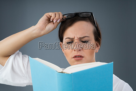 young woman trying to read book