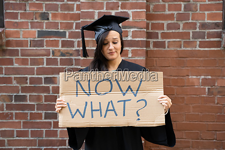 sad graduate student standing with now