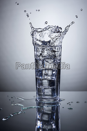 ice splashes into water glass