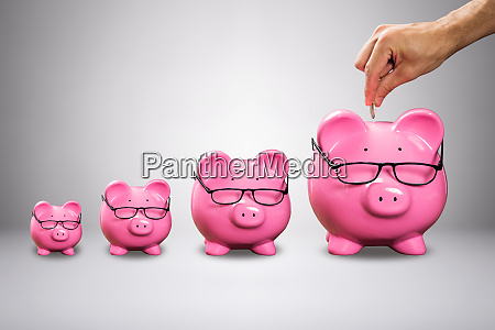 man inserting the coin in piggybank