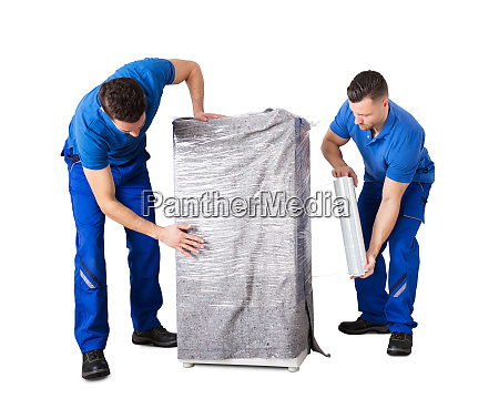male movers wrapping the home appliances