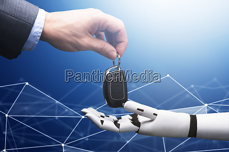 businesspersons hand giving car key to