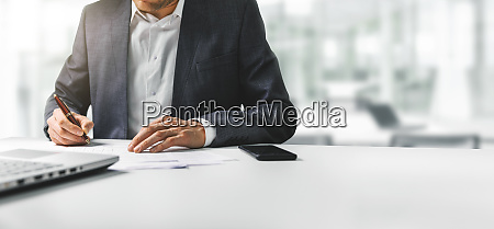 businessman signing business contract papers in