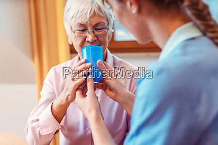 caregiver helping senior woman drinking giving