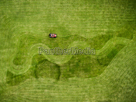 aerial photography of man on lawnmower