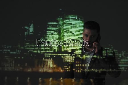double exposure businessman against highrise lights