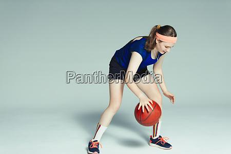 teenage girl basketball player dribbling ball
