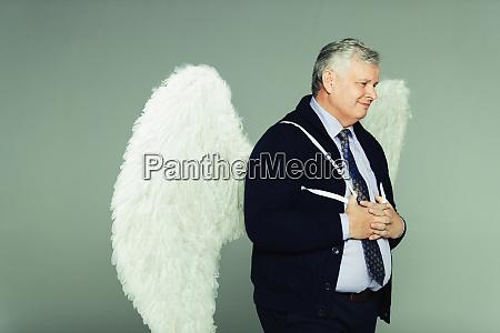 smiling businessman wearing angel wings