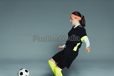 teenage girl soccer player kicking soccer