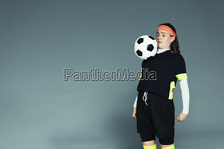 teenage girl soccer player balancing ball