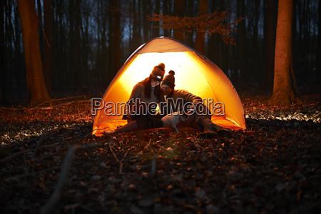couple using digital tablet inside glowing