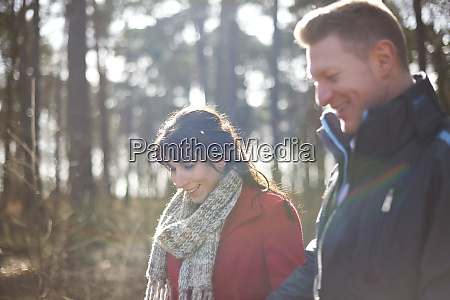 couple hiking in sunny autumn woods