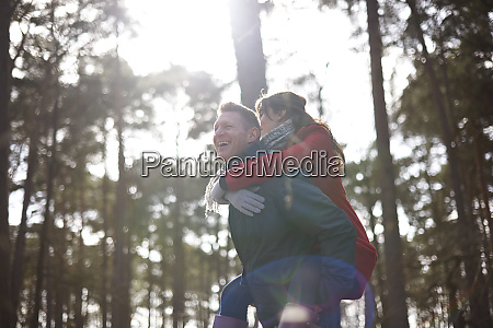 happy playful couple piggybacking in sunny