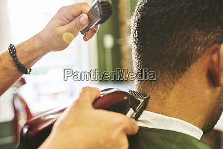 close up male barber using trimmer